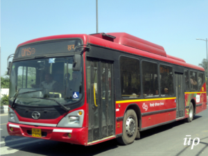 A red AC bus being utilized by Delhi Transport Corporation.