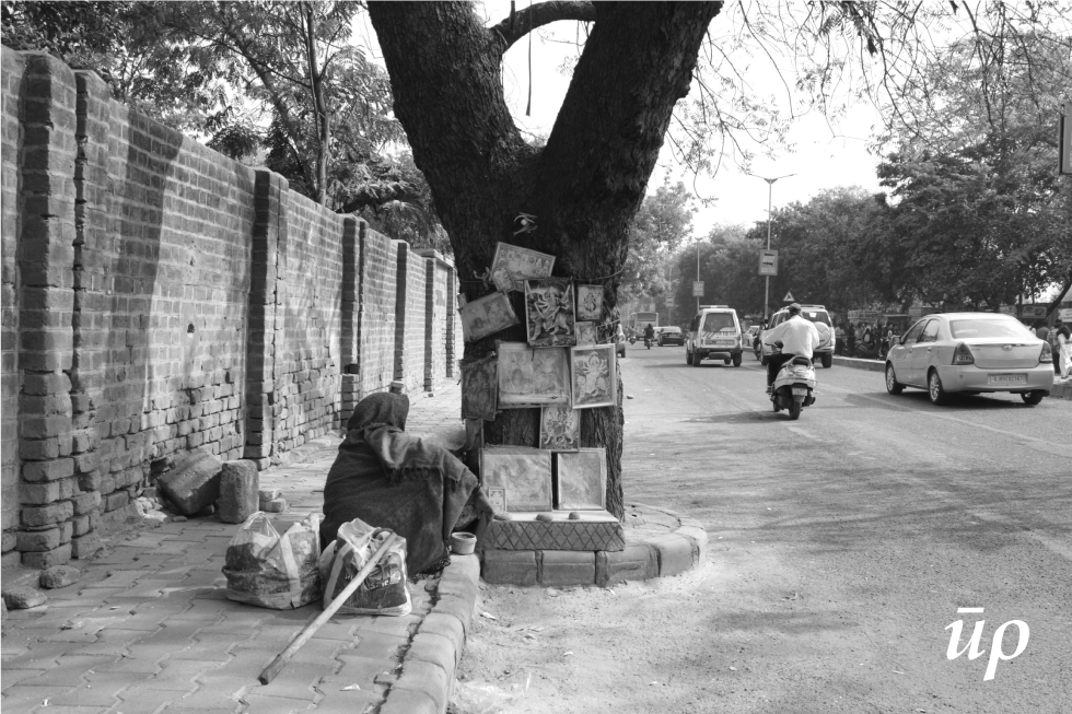 The old Limbdo (Azadirachta indica A.) tree marked as a shrine forms safe interim shelter for the elderly homeless woman during the day. This practice of in-habitation around tree represents typical beginning of roadside tree shrines that forms reoccurring wider pattern on streets.